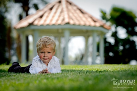 Outdoor toddler portrait in the grass in front of the gazebo